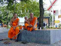 monks sitting resting outside wat pra thong temple in phuket, thailand