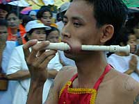 man having a instrument through his cheek during a parade in Phuket town