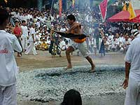 Man walking on burning coal during 1 of the festival days in Phuket vegetarian festival