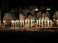 A family surounded of live candles sitting on a beach in Phuket during the last evening of Phuket Vegetarian Festival in Phuket, Thailand